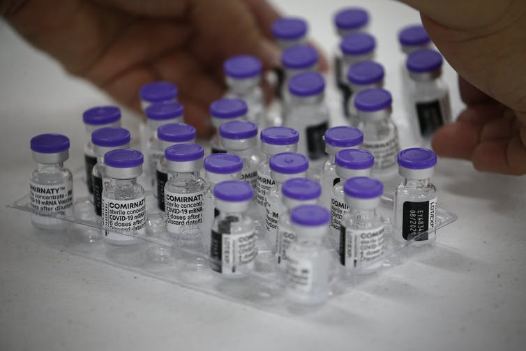 Vials of the Pfizer vaccine being prepared for delivery
