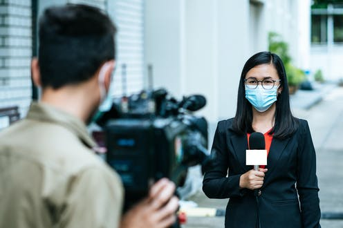 Journalist and cameraman shooting outdoor news update while wearing mask prevent Covid-19 or coronavirus quarantine pandemic.