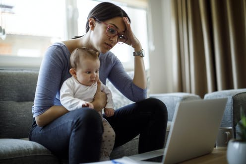 Mother holds baby in lap while working on computer