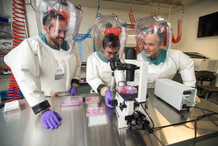 three men in full PPE gather around lab equipment