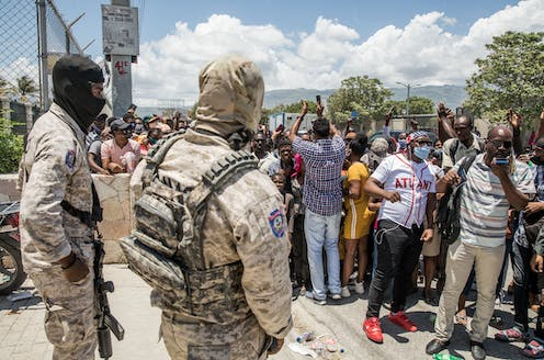 Police look on as Haitian citizens gather.