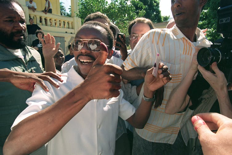 Father Jean-Bertrand Aristide holds up his thumb covered in ink after voting.