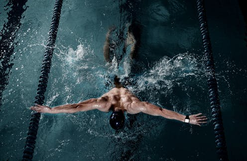 A swimmer wearing a watch is doing the butterfly stroke