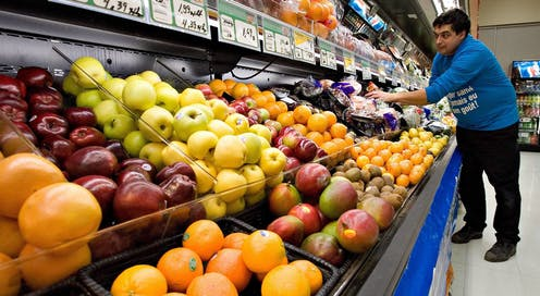 A grocery store worker tends to rows of fruit and vegetables.