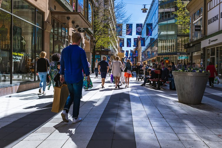People shop on a sunny Stockholm street.