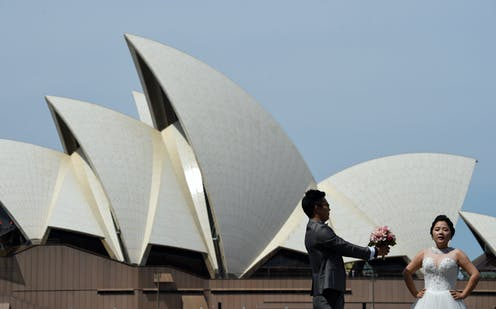 Bride and groom pose in front of the Sydney Opera House.