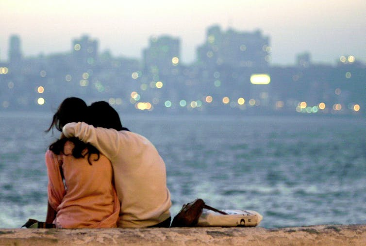 Couple hug as they look at a river view.
