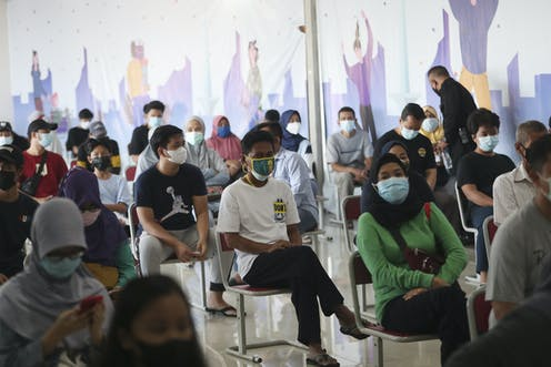 People in Indonesia sit on chairs, waiting for vaccines.
