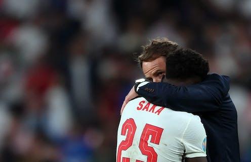 England coach Gareth Southgate embraces player Bukayo Saka after he missed a key penalty kick