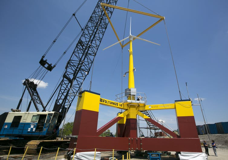 People stand next to a small wind turbine held by a crane. Just the base is three times higher than a human.