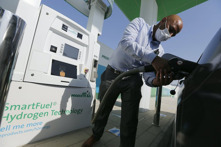 A man filling a vehicle fuel tank from a hydrogen pump