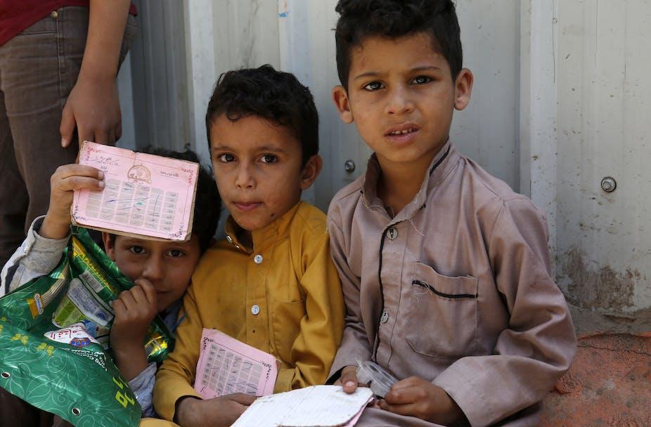 Three Yemeni children shown waiting for food rations.