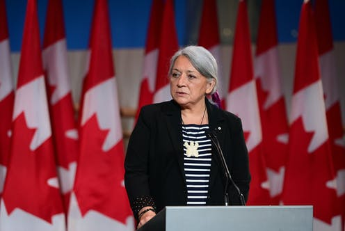A woman stands in front of a bunch of canada flags behind a podeium