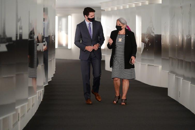 A man and a woman, both wearing masks, walk down a hallway