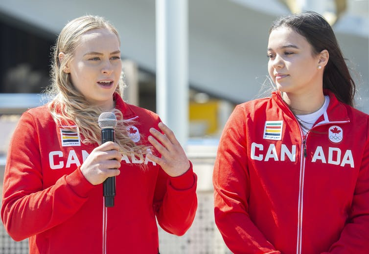 Waist-up shot of two women wearing red zip-up jackets with CANADA spelled across the front.