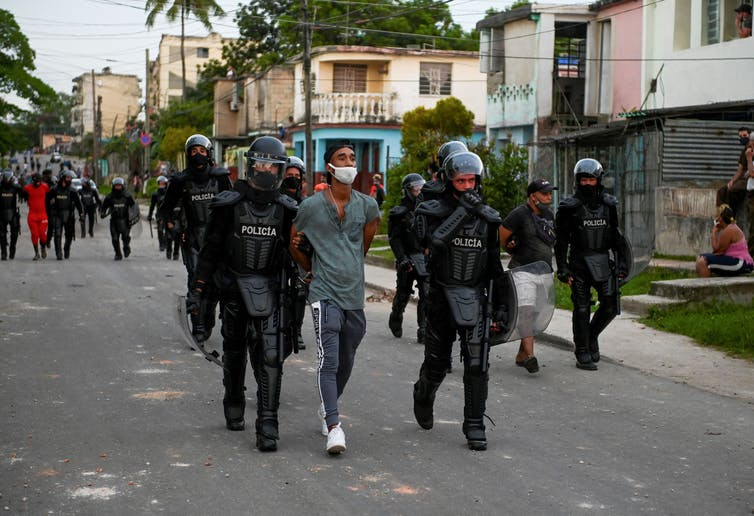Police in riot gear walk man in handcuffs down the street