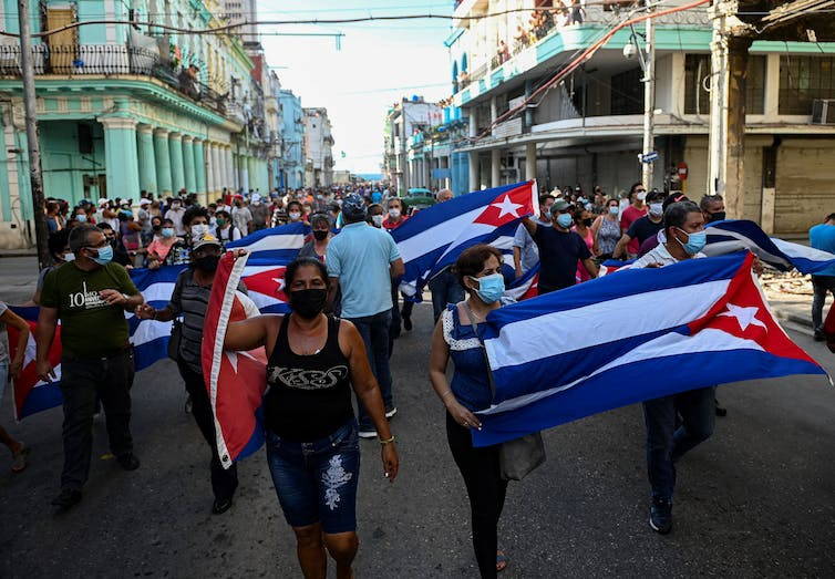 People march down the streets of Havana holding Cuban flags
