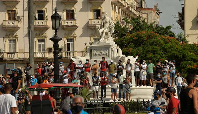 People stand at the base of a statue