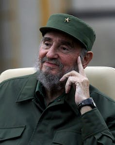 Picture of an aged Fidel Castro in olive army garb, smiling slightly