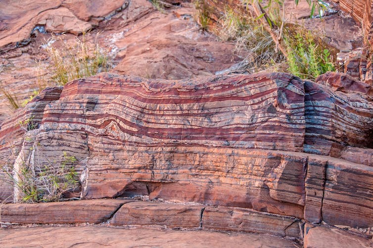 Red and brown bands along a rock face