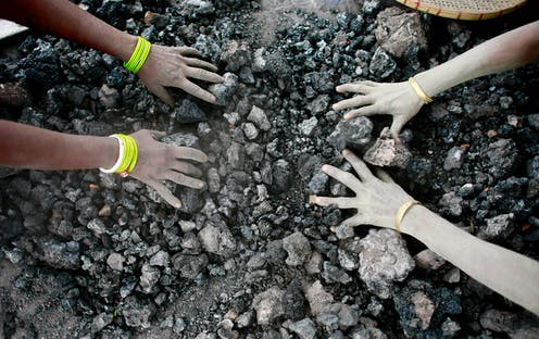 hands touching coal pieces