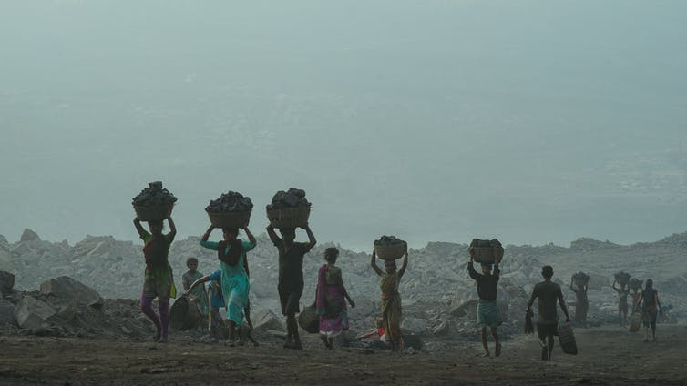 people carry baskets filled with coal