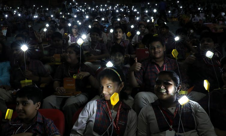 students hold lights