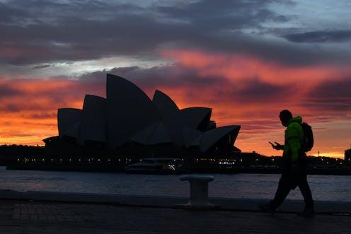 Man walks past Sydney Opera House at dusk.