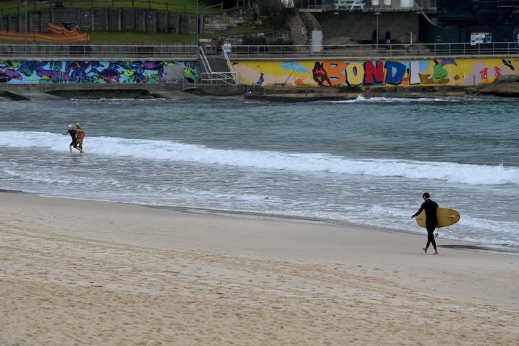 Surfer walks along Bondi beach.