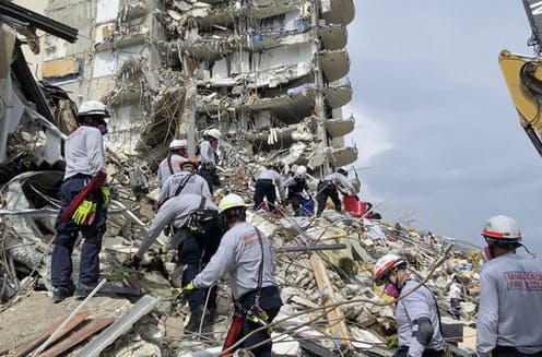 Rescuers search for survivors in a collapsed building