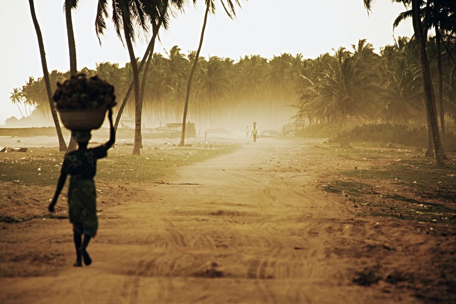 A woman on beach road carrying heavy load.