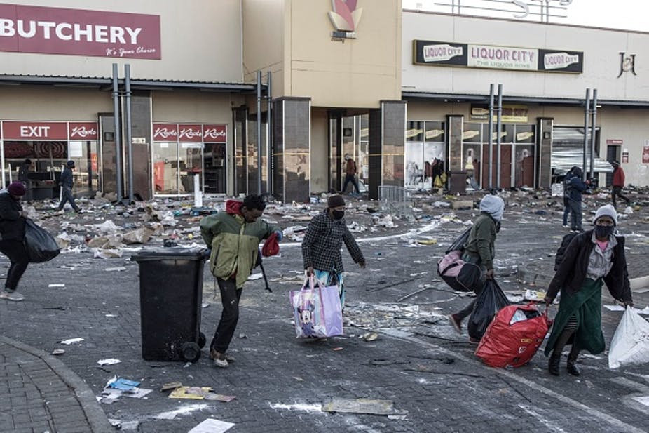 People walk away from a shopping centre, carrying bags and a rolling bin. Trash lies all over the ground.