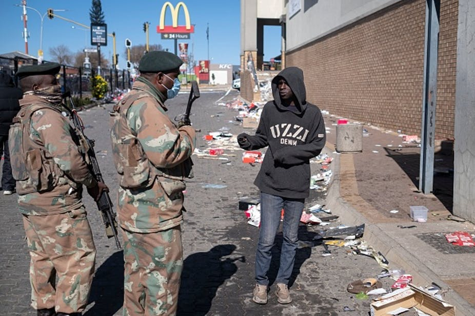 Two armed men in camouflage uniform speak to a civilian outside a large building. Trash scattered on the road.