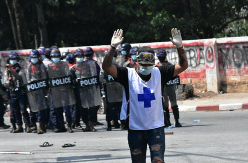 A medic walks away from a line of police with hands raised