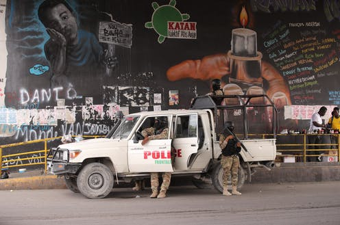 Police officers deploying in front of a political mural in the capital of Haiti, Port-au-Prince, July 2021.