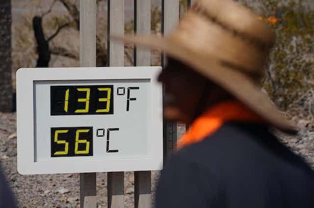 Un homme passe devant un panneau indiquant 56 degrés celcius.