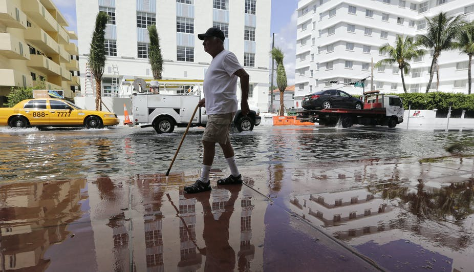 A man with a cane walks on a wet sidewalk next to a flooded street under blue skies