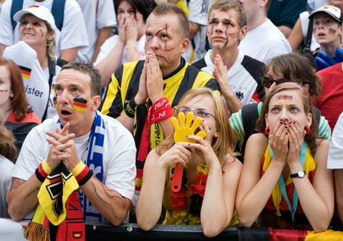 German football fans put their hands over their faces