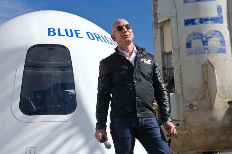 A white man stands in front of a rocket reading 'BLUE ORIGIN'