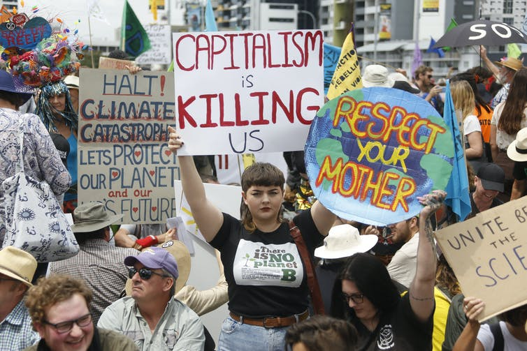 Placards at an environmental protest, one of which reads 'capitalism is killing us'