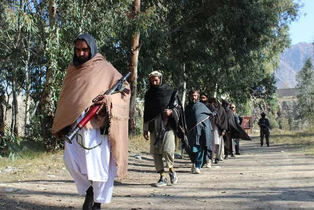 Men in robes with covered heads walk with weapons on a tree-lined dirt road; a soldier can be seen in the background.