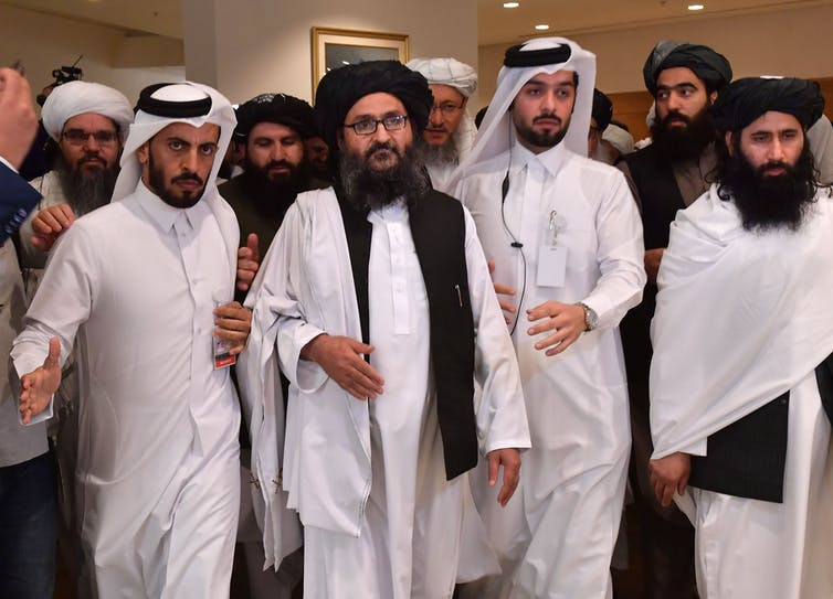 Bearded men in white robes and head coverings walk closely together in a hotel-like setting