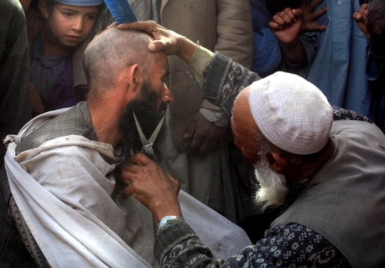 A street hairdresser in Kabul cuts a man's beard in November 2001 after the fall of the Taliban regime.