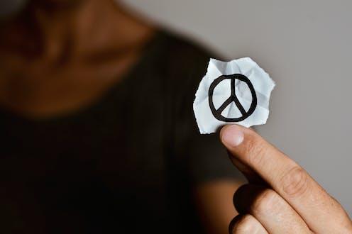 Una mano sujeta un papel con un símbolo de la no violencia dibujado.