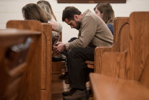 People bow their heads in prayer during a Sunday evening service at Grace Orthodox Presbyterian Church in Lynchburg, Virginia.