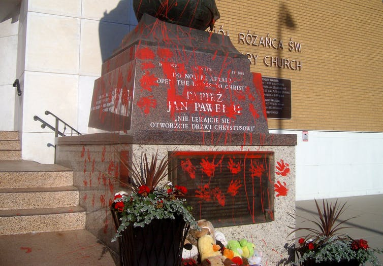 A statue of the late Pope John Paul II, standing at the Holy Rosary Catholic Church, has been vandalized with red paint splatter and handprints
