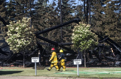 Firefighters walk past the remains of a Catholic church that was on fire, with trees in the foreground and parking signs that read 'reserved for parish staff'
