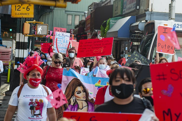 Street protest of people wearing face masks and holding signs demanding rights