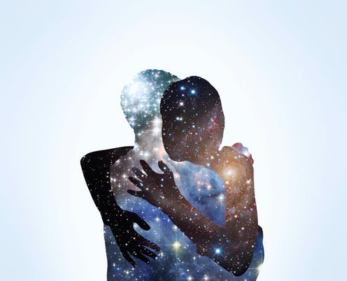 Two people hugging. Each one looks like they are made of stars in the night sky.