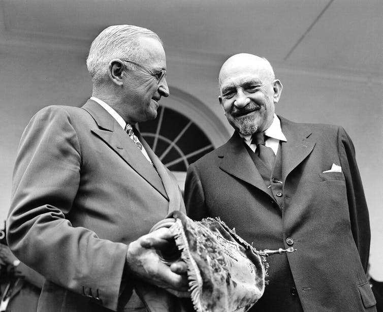 U.S. President Harry S. Truman holds a copy of the Torah, presented to him by Chaim Weizman, right, in Washington on May 25, 1948.